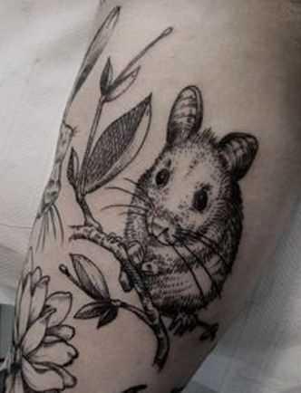 Tatuagem no ombro da menina do mouse em um galho