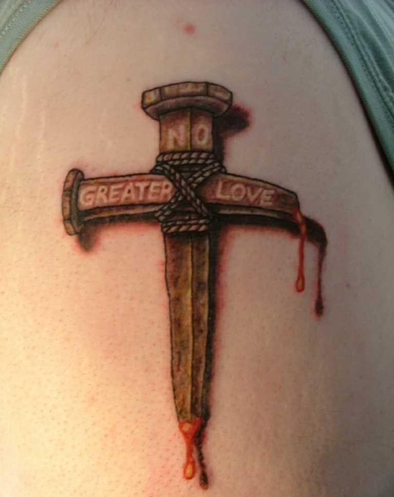 Tatuagem no ombro da menina em forma de cruz