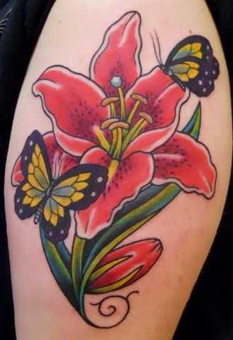 Tatuagem no ombro da menina em forma de lírio e borboletas