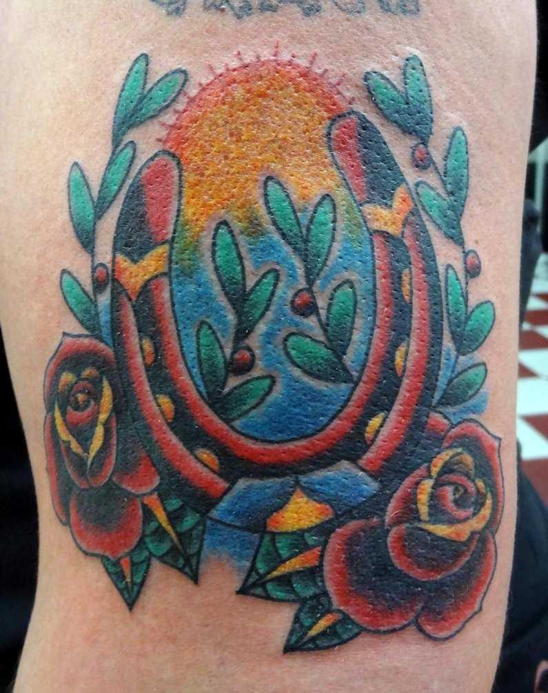 Tatuagem no ombro da menina - ferradura, a rosa e o sol