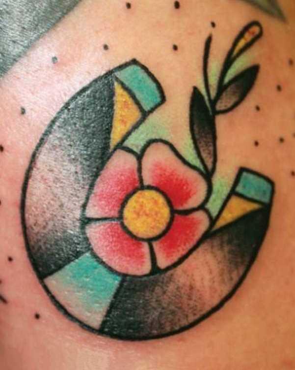 Tatuagem no ombro da menina - ferradura e a flor