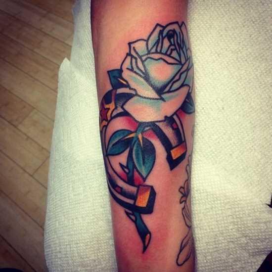 Tatuagem no ombro da menina - ferradura e rosa
