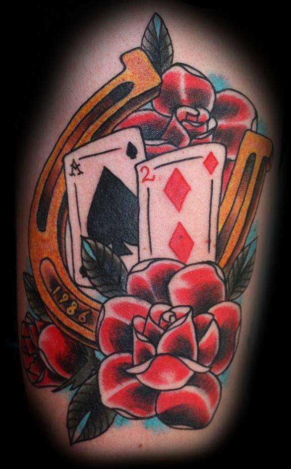 Tatuagem no ombro da menina - ferradura, mapas e rosa