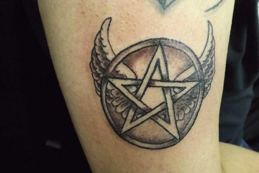Tatuagem no ombro da menina - o pentagrama com asas