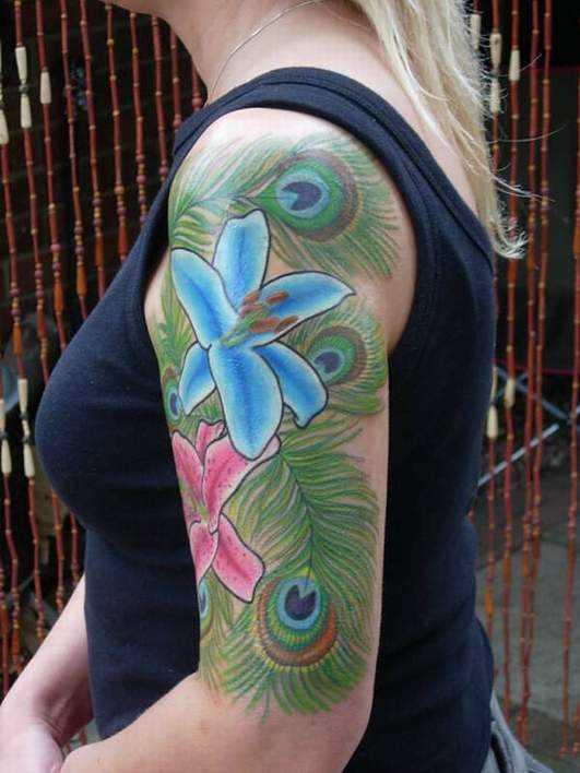 Tatuagem no ombro da menina - pena de pavão e lírio do vale