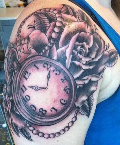 Tatuagem no ombro da menina - relógio de bolso e rosas
