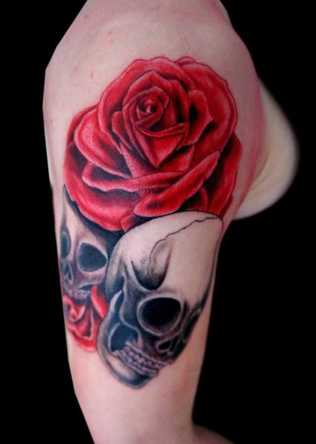 Tatuagem no ombro da menina - rosa e dois crânios