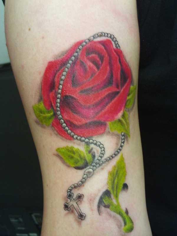 Tatuagem no ombro da menina - rosa e um colar com uma cruz