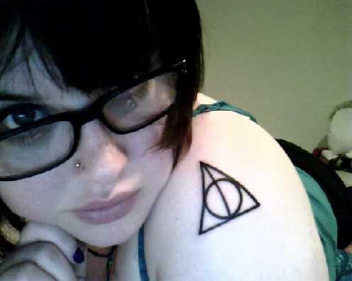 Tatuagem no ombro da menina - triângulo e círculo