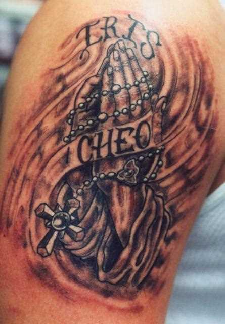 Tatuagem no ombro de um cara - a cruz com corrente em palmas