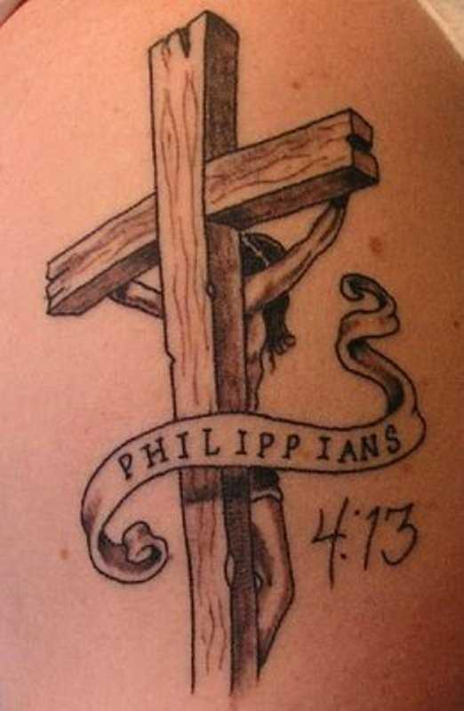 Tatuagem no ombro de um cara - a cruz com o crucificado nele Jesus e inscrição