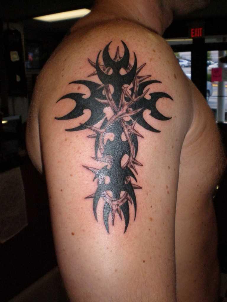 Tatuagem no ombro de um cara - a cruz e a coroa de espinhos