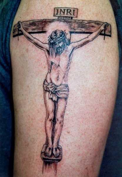 Tatuagem no ombro de um cara - a cruz e Jesus, que foi crucificado nele
