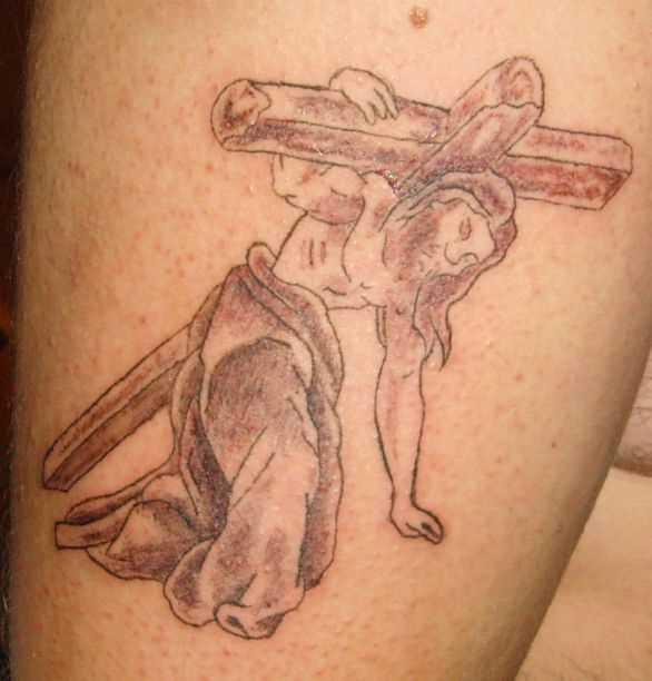Tatuagem no ombro de um cara - a cruz e Jesus, tendo-o