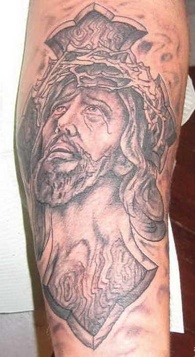 Tatuagem no ombro de um cara - a cruz e o rosto de choro de Jesus