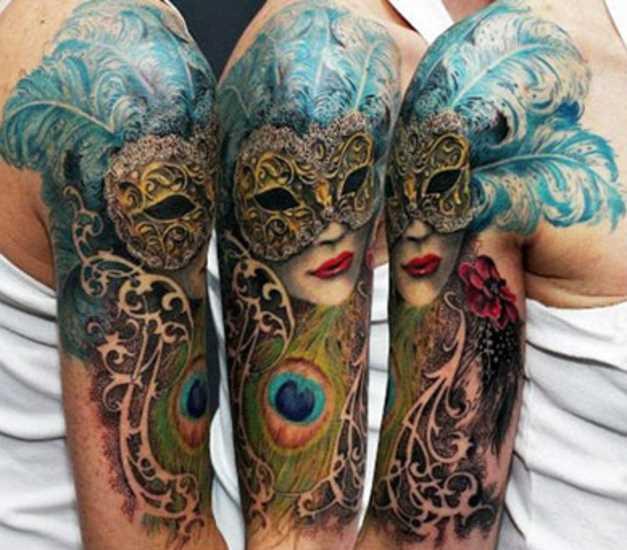 Tatuagem no ombro de um cara - a menina para dentro da máscara e penas de pavão