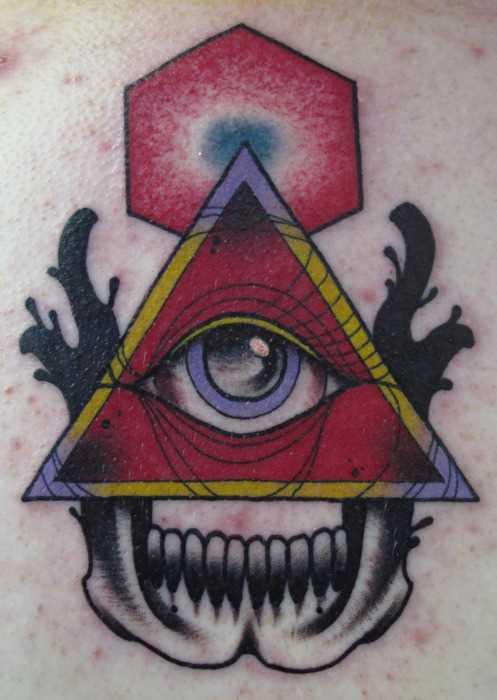 Tatuagem no ombro de um cara - a pirâmide com o olho e o crânio