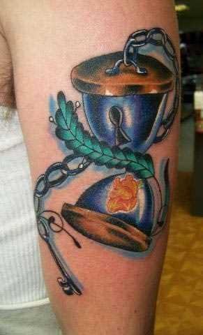 Tatuagem no ombro de um cara - circuito, a ampulheta e a chave