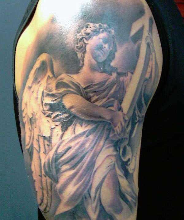 Tatuagem no ombro de um cara como imagem de um anjo com uma cruz