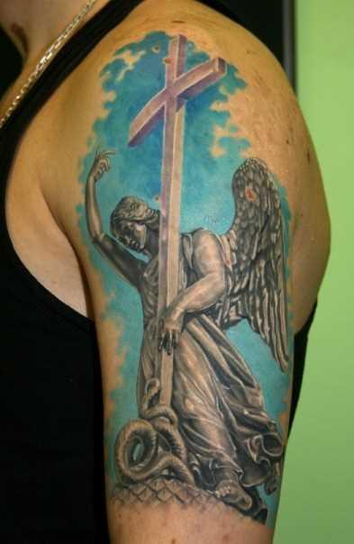 Tatuagem no ombro de um cara - de- anjo com a cruz