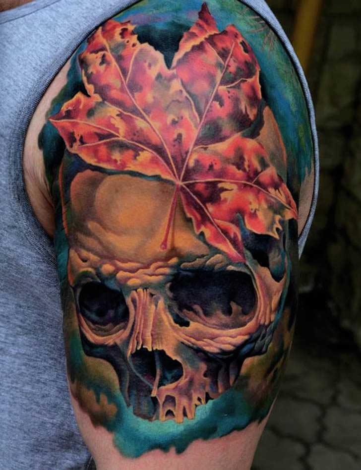 Tatuagem no ombro de um cara de crânio e folhas