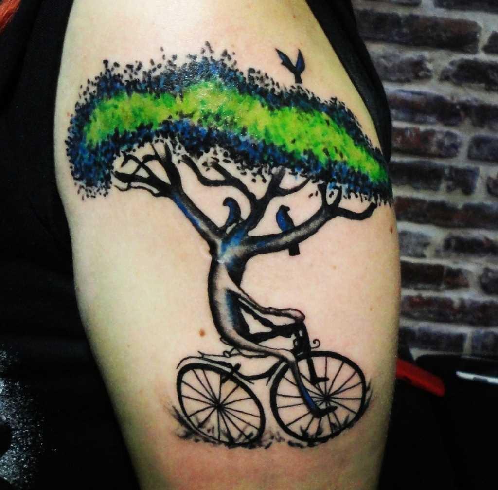 Tatuagem no ombro de um cara - de madeira em bicicleta