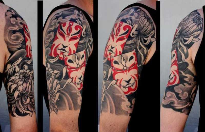 Tatuagem no ombro de um cara - de máscara e de crisântemo