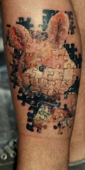 Tatuagem no ombro de um cara - de quebra-cabeça em forma de coelho