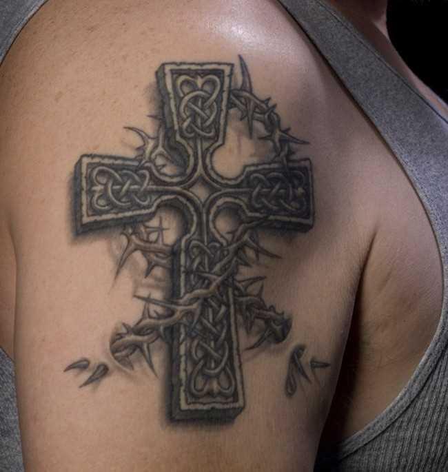 Tatuagem no ombro de um cara em forma de cruz e a coroa de espinhos