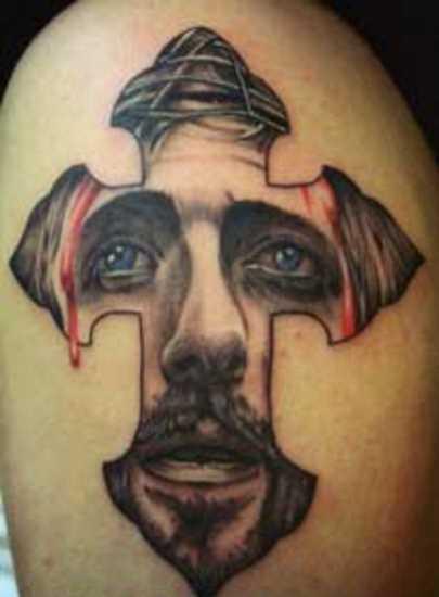 Tatuagem no ombro de um cara em forma de cruz e o rosto de Jesus nele