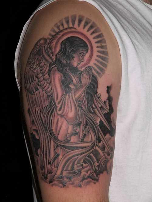 Tatuagem no ombro de um cara em forma de imagem oração do anjo