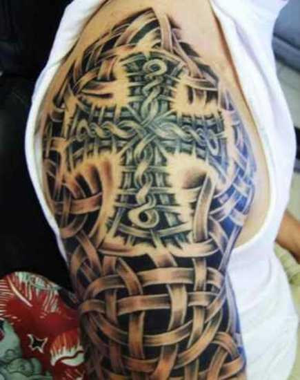 Tatuagem no ombro de um cara em forma de uma cruz e de um padrão