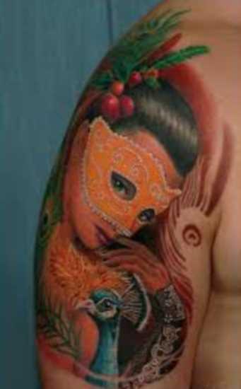 Tatuagem no ombro de um cara em uma garota em uma máscara e um pavão