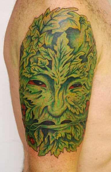 Tatuagem no ombro de um cara - folhas em forma de pessoa
