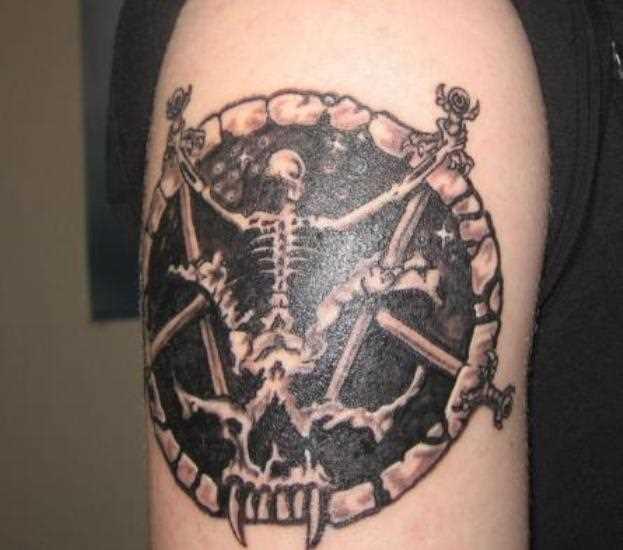 Tatuagem no ombro de um cara - o pentagrama e o esqueleto