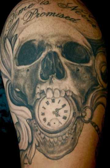Tatuagem no ombro de um cara - relógio de bolso com uma caveira