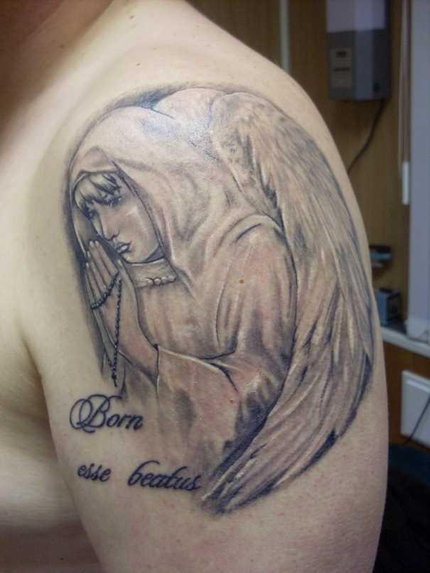 Tatuagem no ombro de um cara - um anjo em forma de menina rezando