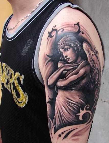 Tatuagem no ombro de um cara - um anjo em forma de menina e padrão de