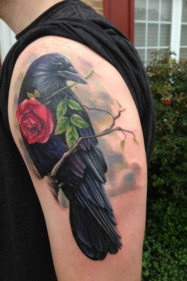 Tatuagem no ombro o homem - corvo com uma rosa