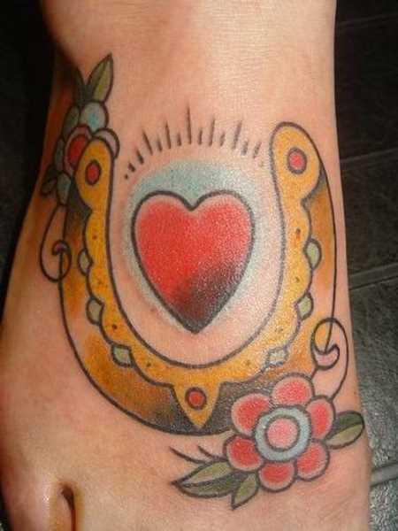 Tatuagem no pé da menina - ferradura, coração e flor