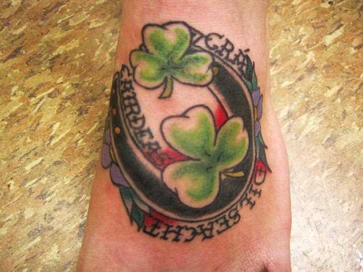 Tatuagem no pé da menina - ferradura, folhas de trevo e inscrição