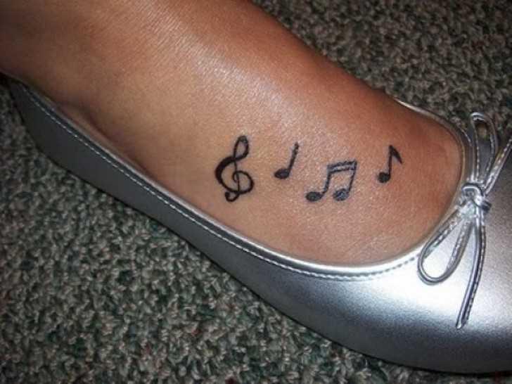 Tatuagem no pé da menina notas e a clave de sol