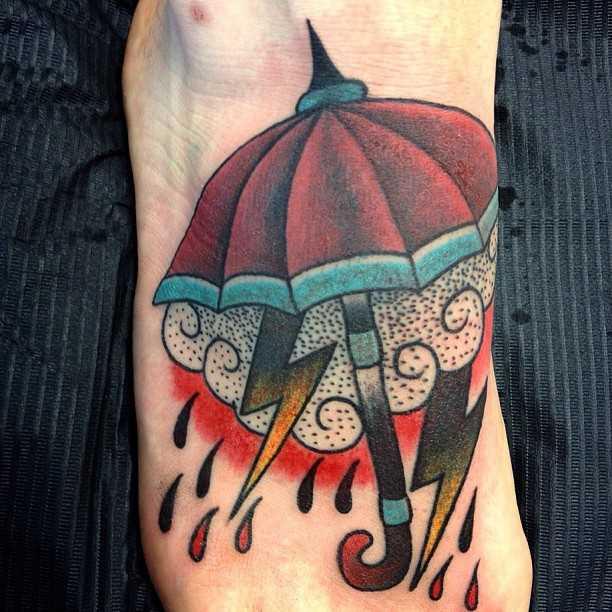 Tatuagem no pé da menina - relâmpago, chuva e guarda-sol