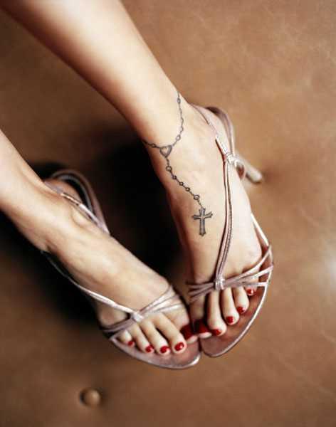 Tatuagem no pé da menina - x vermelho na pulseira