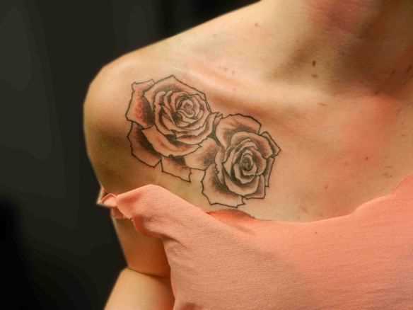 Tatuagem no peito da menina duas rosas