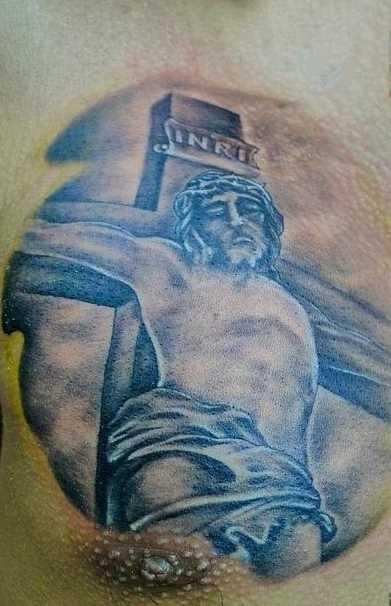 Tatuagem no peito de um cara - a cruz com Jesus crucificado