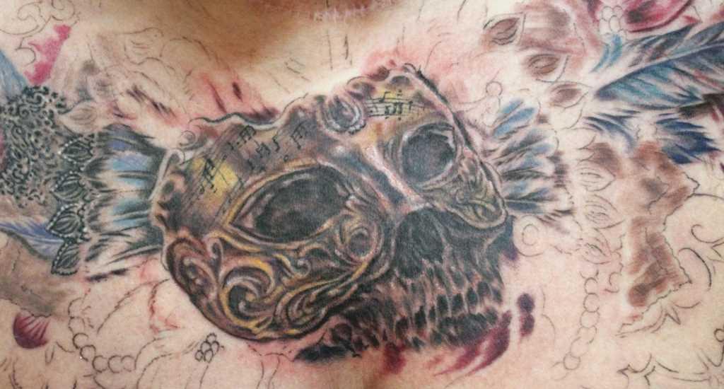 Tatuagem no peito de um cara - a máscara, o crânio e as penas