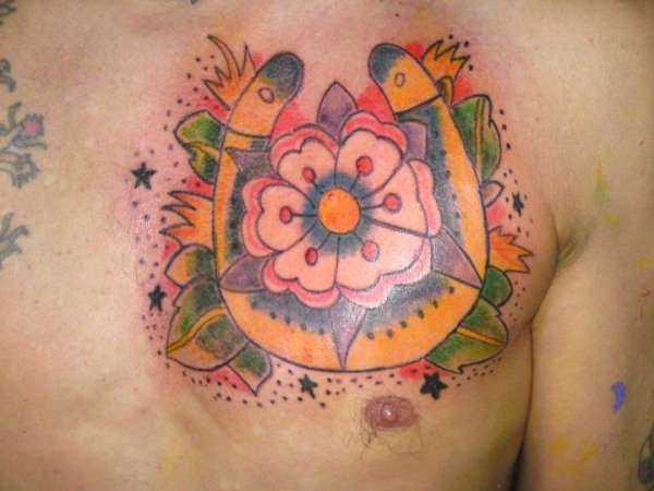 Tatuagem no peito de um cara - de- ferradura e a flor