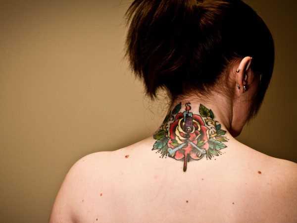 Tatuagem no pescoço de menina rosa e uma vela