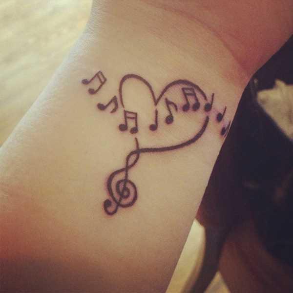 Tatuagem no pulso da menina - as notas da clave de sol e o coração